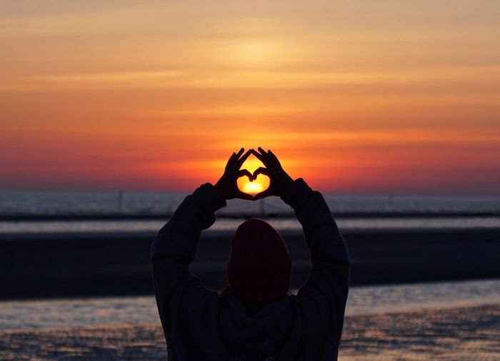 Woman making heart shape at beach against sky during sunset