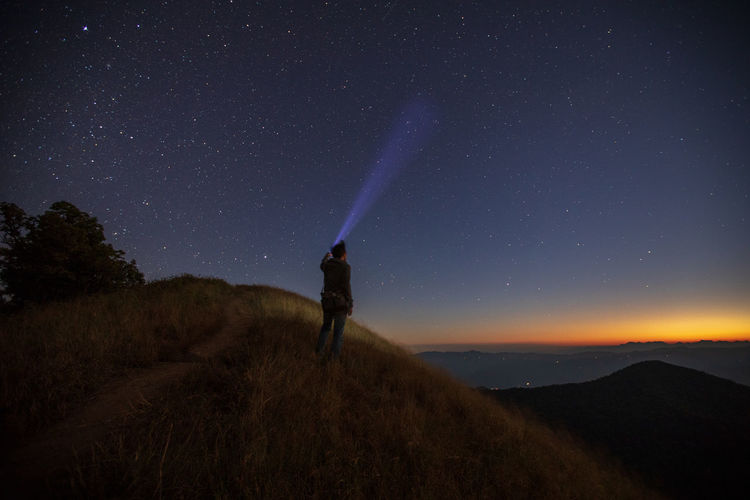 Tourist with illuminated flashlight standing on mountain against star field at night