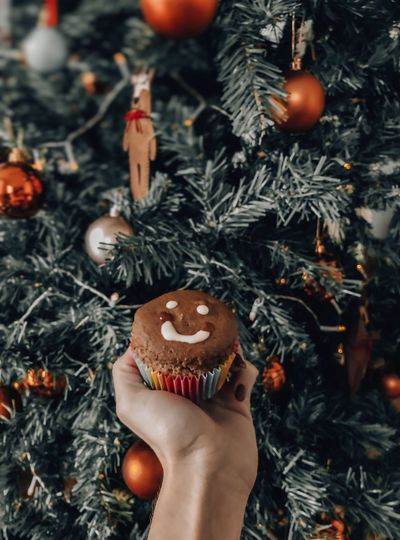 Cropped hand holding muffin by christmas tree