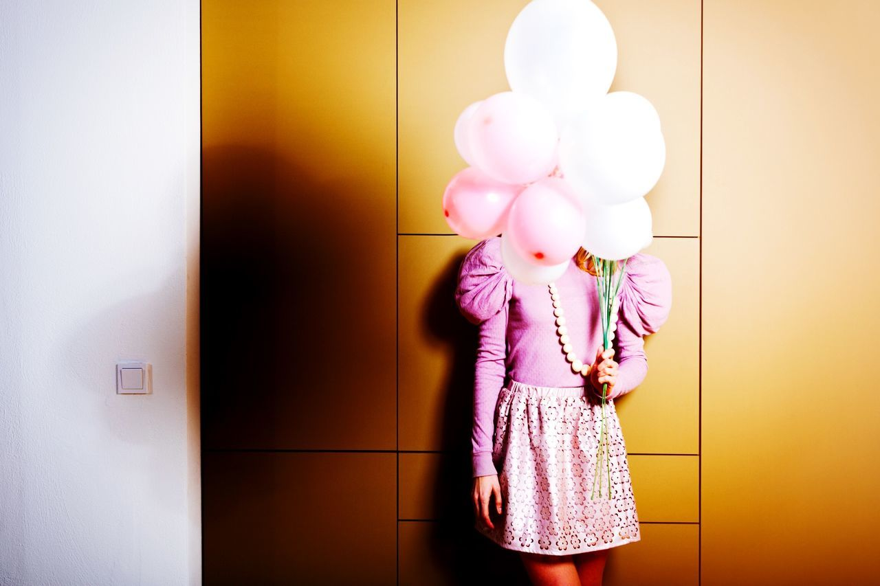 Woman holding balloons in front of her face
