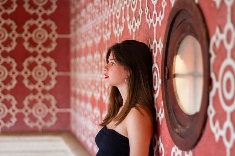 Portrait of woman against red wall
