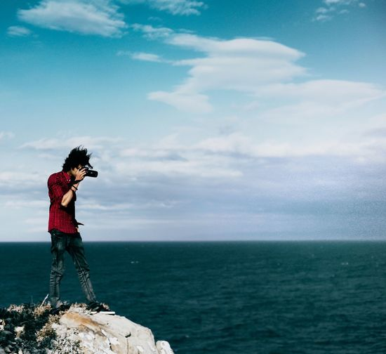 Photographer Standing On Rock Over Sea Against Sky