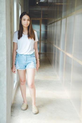 Portrait of young woman standing in corridor