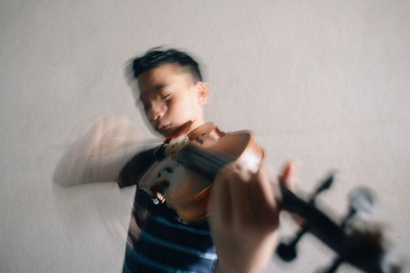 An asian boy playing violin against a wall