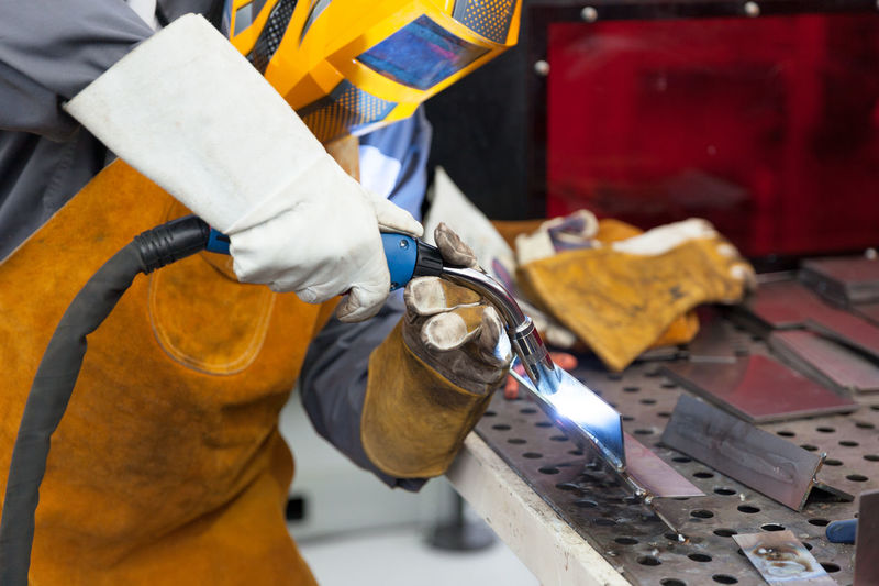 Close-up of man working on metal in workshop