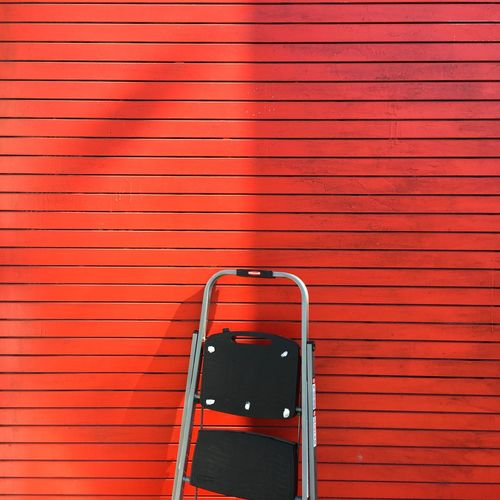 View Of Ladder Next To Red Wall