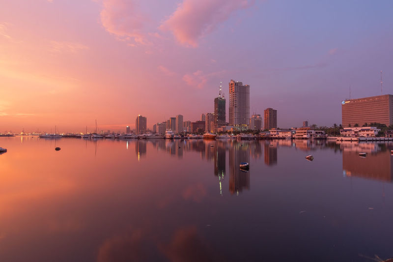 Reflection of buildings in city against sky during sunset