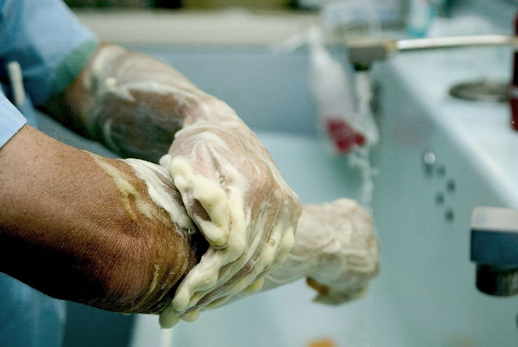 Close-up of medical doctor washing arms and hands