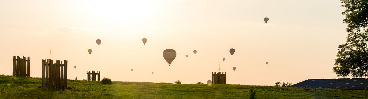 Many hot air balloons fly of in to the distance at sunset over the Worcestershire countryside as part of the Ragley Hall based Air Festival 2018. Event Adventure Air Vehicle Balloon Environment Festival Flying Freedom Grass Hot Air Balloon Landscape Mid-air Nature No People Outdoors Panoramic Plant Scenics - Nature Sky Sun Sunset Transportation Travel Destinations
