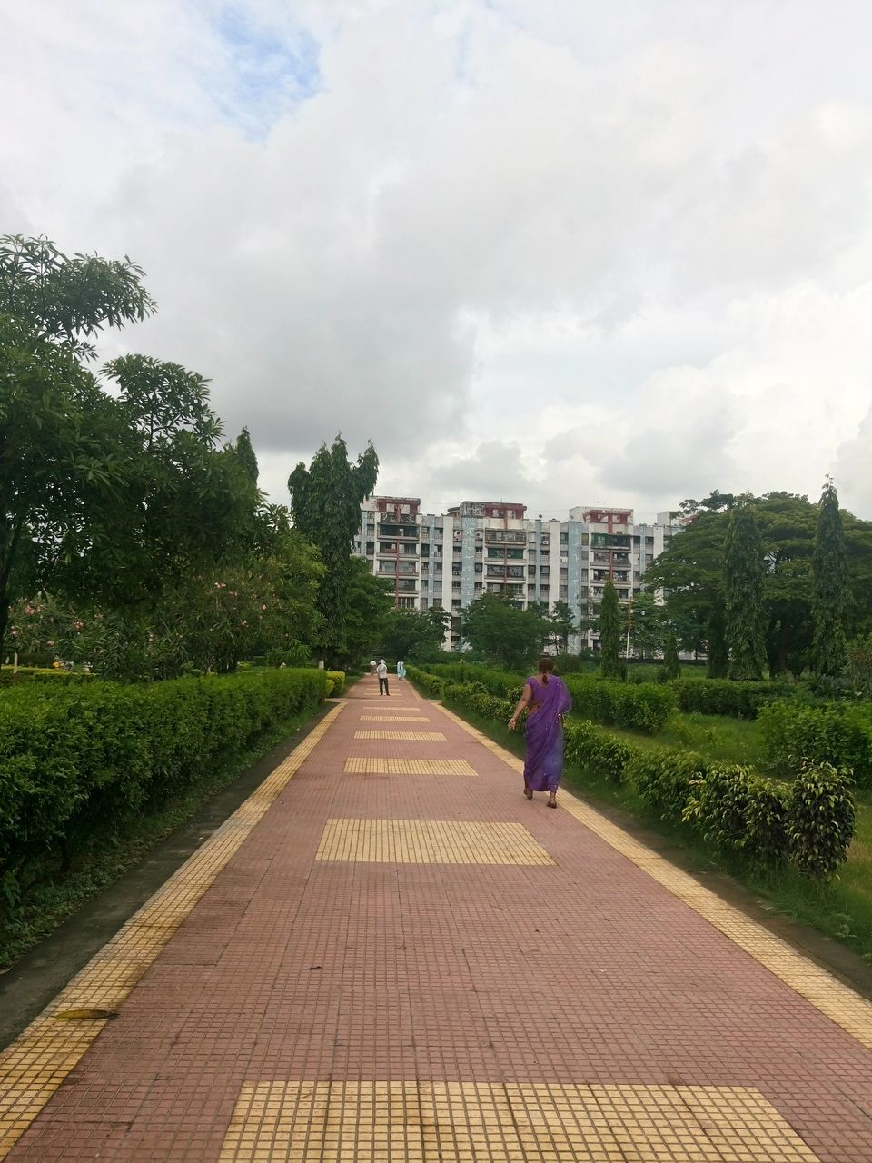 rear view, sky, built structure, cloud - sky, walking, architecture, real people, full length, building exterior, tree, the way forward, day, outdoors, women, growth, two people, nature, men, people