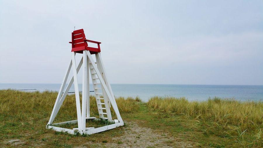 Lifeguard chair against sea