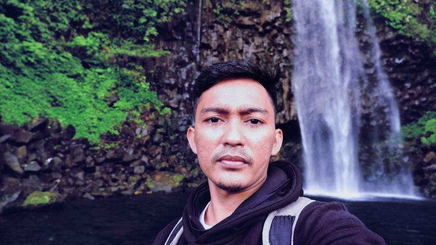 Portrait of man against waterfall in forest