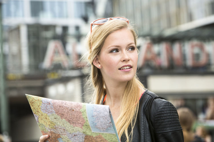 Woman holding map while looking away