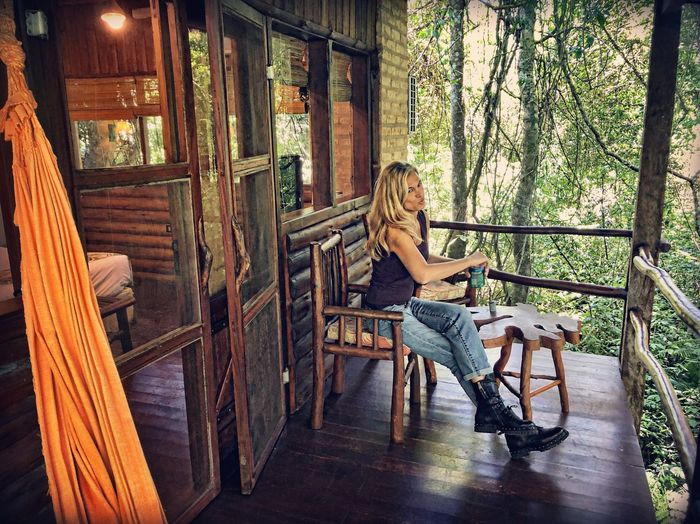 Jungle Lodge Tropical One Person Women Sitting Real People Seat Tree Full Length Young Adult Young Women Architecture Leisure Activity Indoors  Side View Day Railing Beautiful Woman Adult Casual Clothing Lifestyles Chair