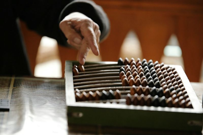 Midsection of man playing with abacus at table