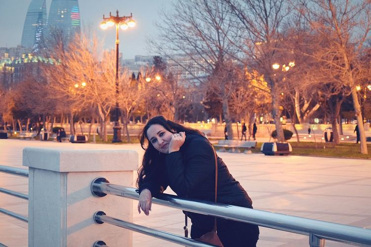 Portrait of smiling woman leaning on railing against illuminated street lights during sunset