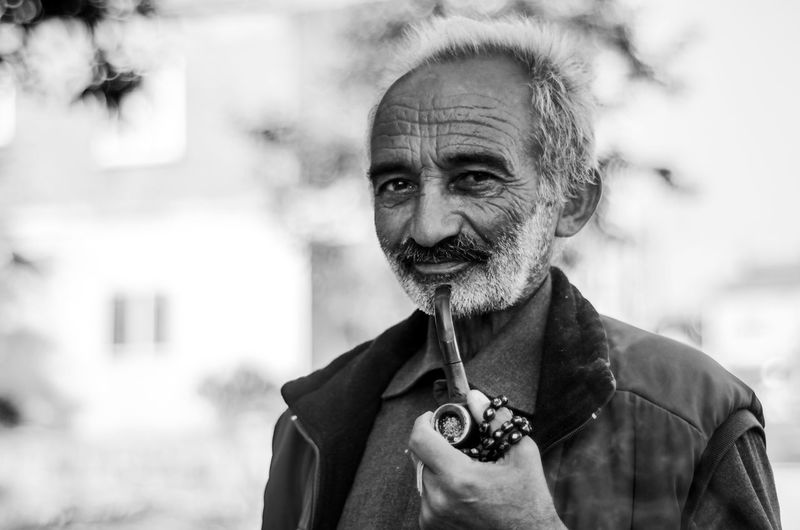 Portrait of senior man holding smoking pipe while standing outdoors