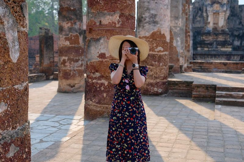 Woman photographing with camera against columns