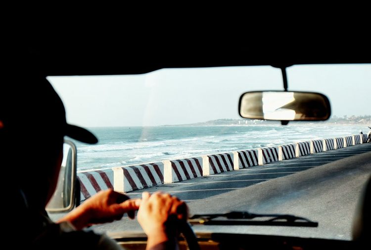 Close-up of man driving car on road against sea