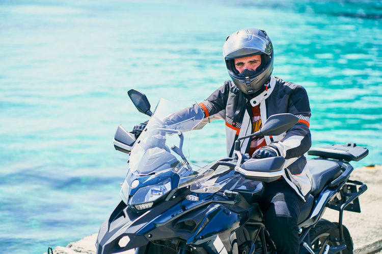 Portrait of man riding motorcycle on sea