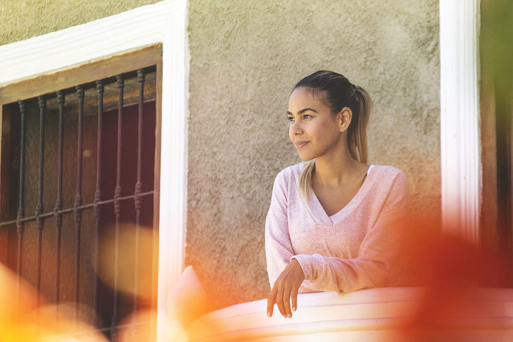 Portrait of woman looking away while sitting on window