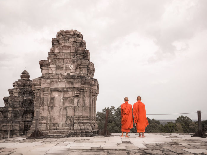 Rear view of monks standing by built structure
