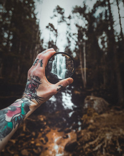 Cropped tattooed hand holding glass in front of waterfall