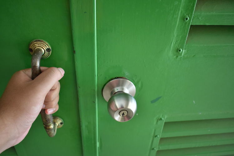 Cropped hand holding door handle