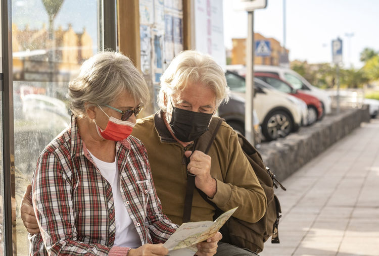 Senior couple wearing mask looking at map in city