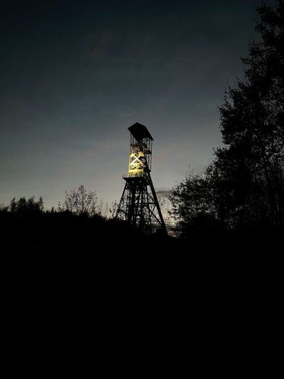 Low angle view of silhouette water tower against sky during sunset