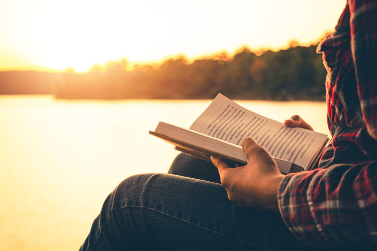 Woman reading book while sitting by lake against sky during sunset