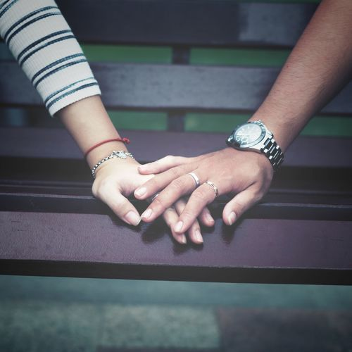 Cropped image of couple holding hands on bench