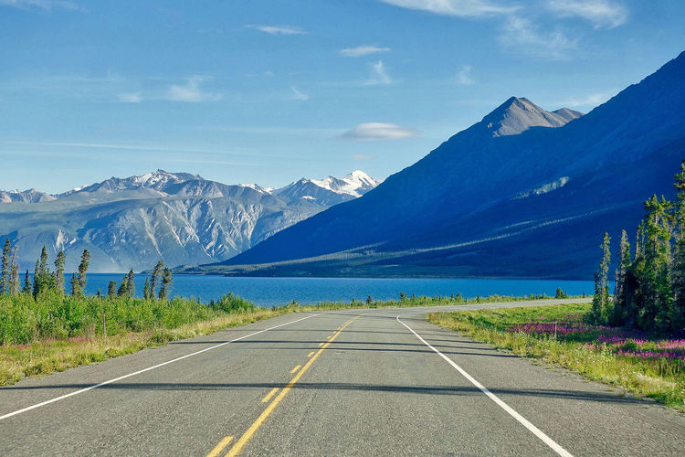 At Kluane Lake in Canada. Grass Kluane Lake Road Trees Yukon Beauty In Nature Bushes Canada Clouds Day Diminishing Perspective Lake Mountain Range Mountains Nature No People Outdoors Road Marking Scenics Sky The Way Forward Tranquil Scene Tranquility Transportation White Line
