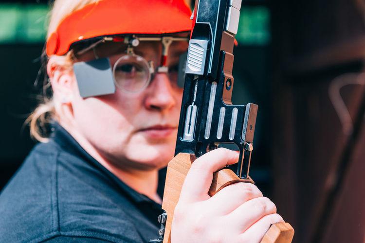 Close-up portrait of woman holding gun