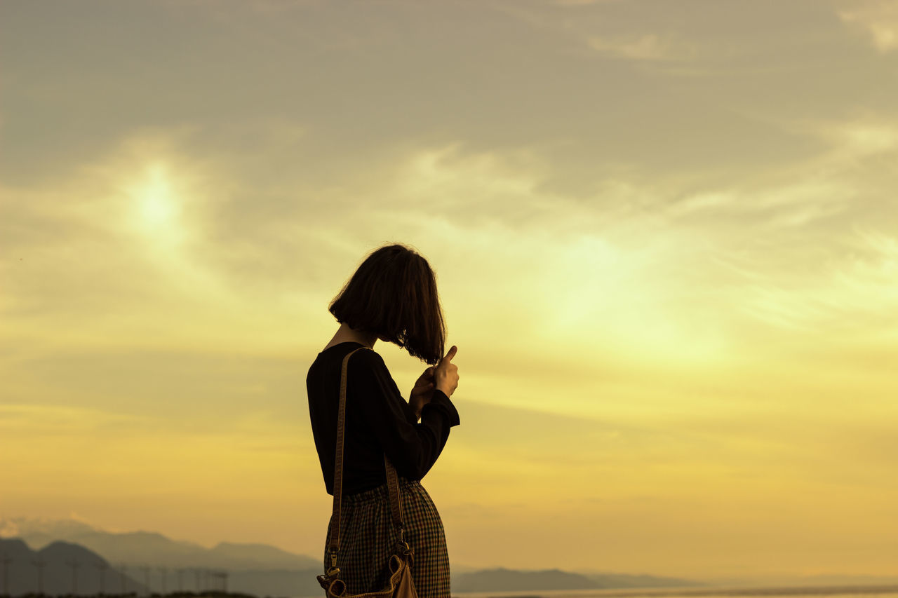 Silhouette Of Woman Standing Against Sky During Sunset