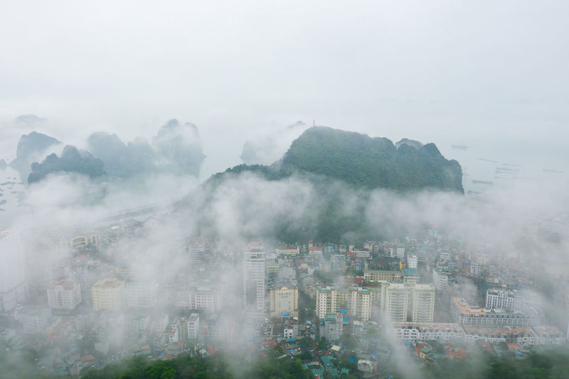 Aerial view of cityscape and rock formations during foggy weather