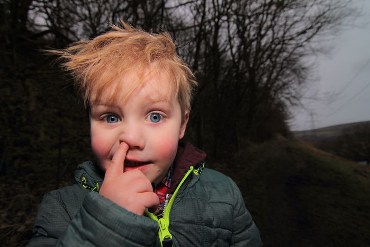 Close-up portrait of boy picking nose
