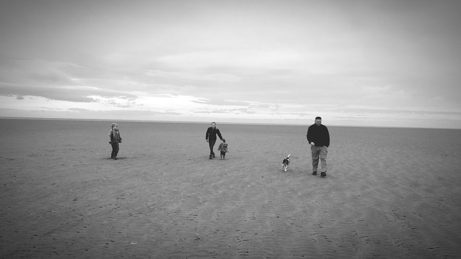 Family With Dog At Beach Against Sky