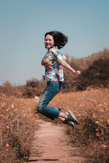 Portrait Of Smiling Young Woman Jumping On Field
