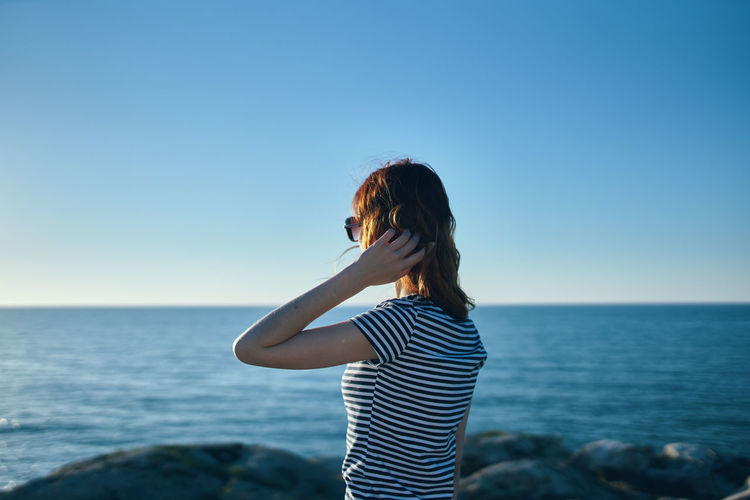 Woman standing in sea against clear sky