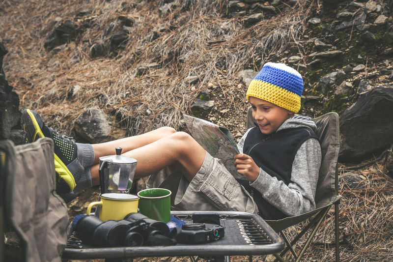 Little boy with headphone with the flag of the Canary Islands sitting with raised legs resting looking on the map of the trails in the forest. young explorer looking for adventure Childhood One Person Real People Child Sitting Lifestyles Leisure Activity Clothing Men Nature Day Boys Knit Hat Males  Casual Clothing Full Length Three Quarter Length Hat Outdoors Innocence Warm Clothing
