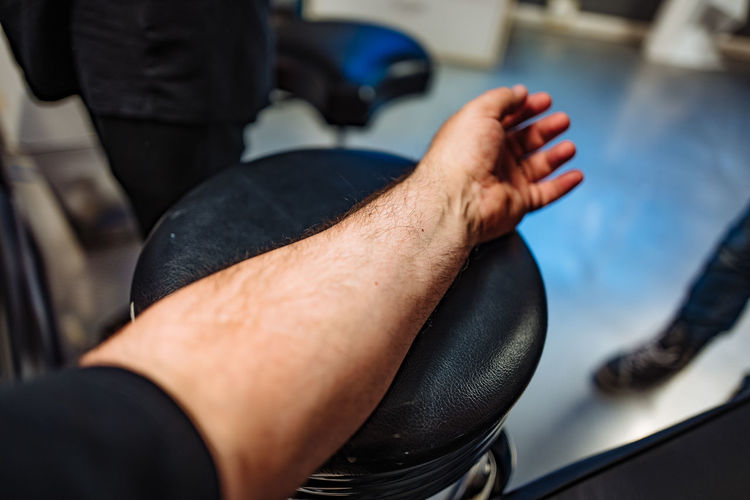 Cropped Image Of Man Resting Hand On Seat At Tattoo Studio