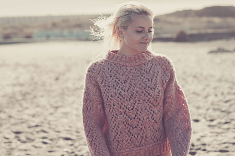 Woman wearing sweater while standing at beach