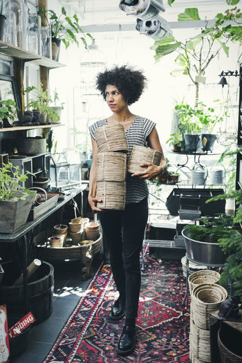 Portrait of woman standing by potted plants