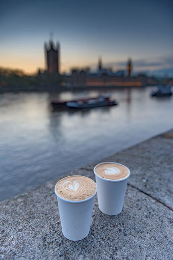 High angle view of cappuccino in glasses on retaining wall by thames river