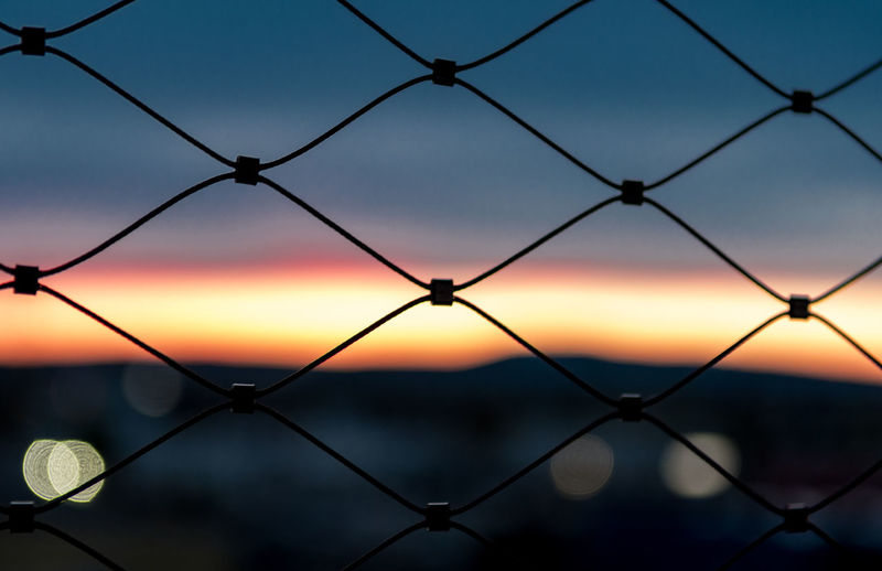 Detail Shot Of Fence Against Scenic Sky