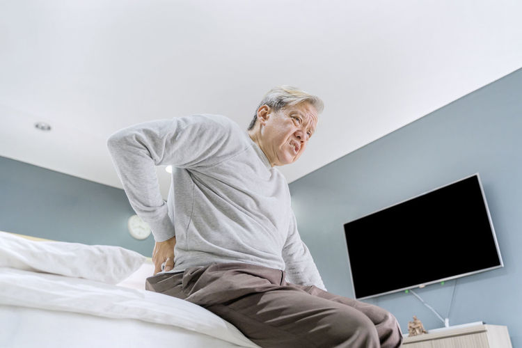 Low angle view of senior man with backache sitting on bed at home