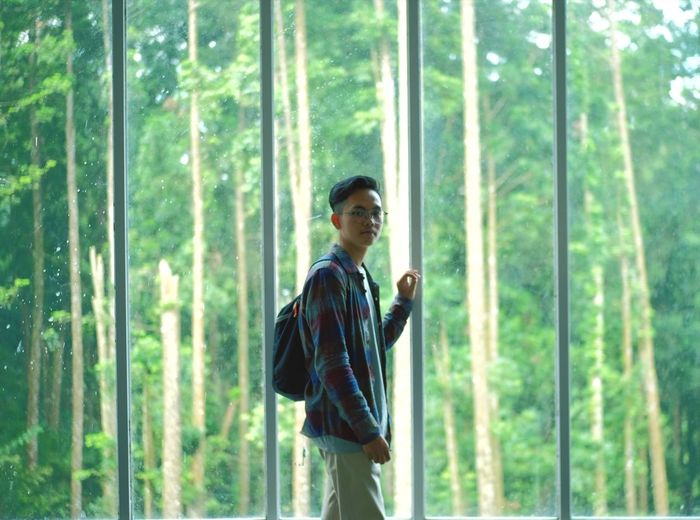 Portrait of young man standing by window in forest