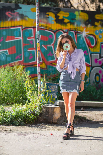 Beautiful woman holding compact disc while standing against graffiti wall
