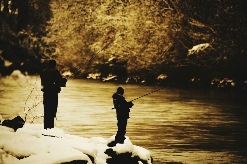 People fishing in lake while standing on snow